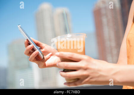 Hispanic woman holding cell phone and iced coffee - Stock Photo