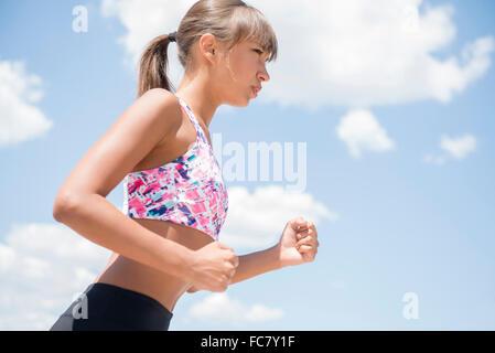 Mixed race woman jogging under blue sky - Stock Photo