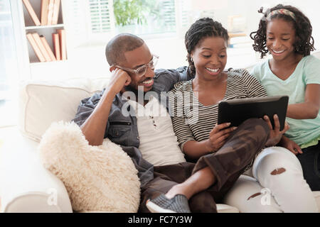 Black family using digital tablet on sofa - Stock Photo