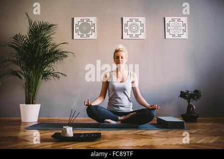 Caucasian woman meditating in yoga studio - Stock Photo