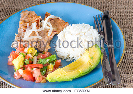 Latin American cuisine fusion: pork steak, white rice,pico de gallo and avocado.Mexican and Cuban cuisine fusion - Stock Photo