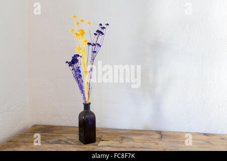 Dried flowers in blue bottle vase on wood - Stock Photo