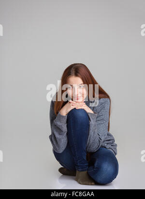 Full length portrait of happy pensive young woman in grey sweatshirt and jeans sitting and thinking over grey background - Stock Photo