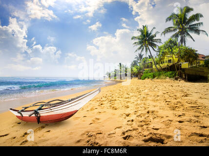 Small boat on a beach of the ocean in Sri Lanka - Stock Photo