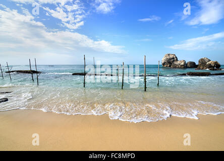 Wooden poles for fishing on a beach of indian ocean in Sri Lanka - Stock Photo