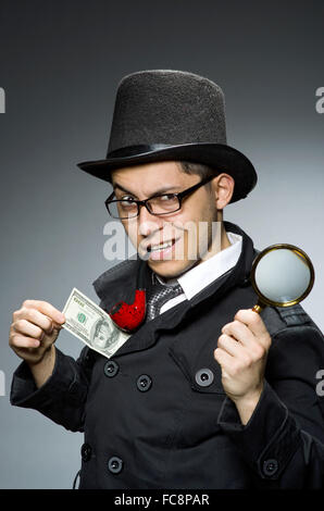 Young detective in black coat with money against gray - Stock Photo