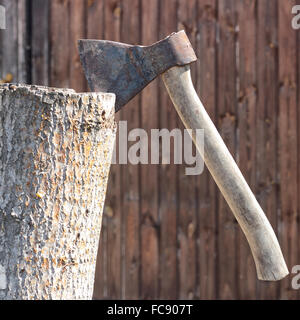Building and repair. A rusty axe in a stub on a wooden background. - Stock Photo