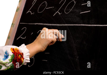 hand of a schoolgirl writing on the chalkboard - Stock Photo