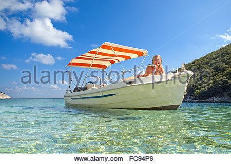 Portrait smiling woman sunbathing on boat in ocean - Stock Photo