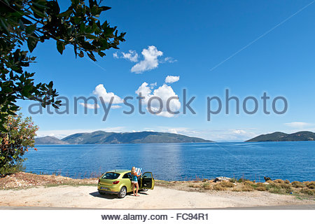 Woman with map next to car at sunny oceanside - Stock Photo