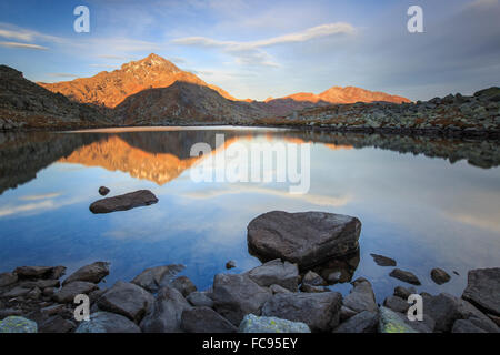 Peak Tambo reflected in Lake Bergsee at dawn, Chiavenna Valley, Spluga Valley, Switzerland, Europe - Stock Photo