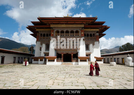 Buddhist monks in stone courtyard of Gangtey dzong (monastery), the largest Nyingmapa monastery in Bhutan, Asia - Stock Photo