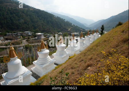 Row of white chortens at the entrance to Rangjung Buddhist monastery in the beautiful hills above Trashigang, Eastern - Stock Photo
