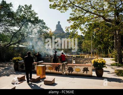 People lighting incense at Po Lin Monastery with Big Buddha statue in background, Lantau Island, Hong Kong, China, - Stock Photo