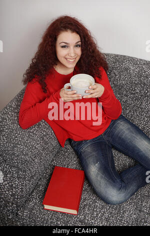 girl drinking a large cup of coffee - Stock Photo