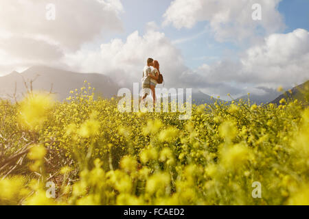 Romantic young couple embracing and kissing on a sunny day outdoors. - Stock Photo