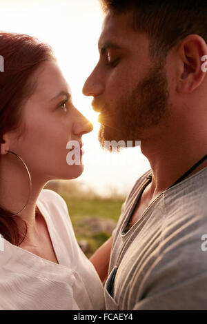 Close up image of young couple in love embracing and looking into each others eyes romantically. Affectionate young - Stock Photo