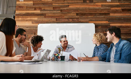 Group of happy young business people meeting in conference room. Team of creative professionals discussing new project. - Stock Photo