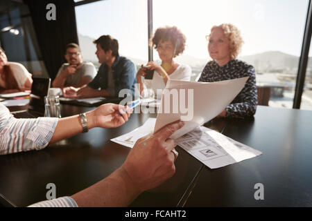 Papers in hands of young man explaining business plan to his creative team. Creative professionals meeting in office. - Stock Photo