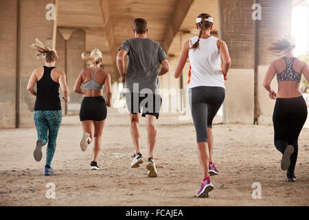 Rear view portrait of group of young people in sports clothing running under a bridge. Runners training together - Stock Photo