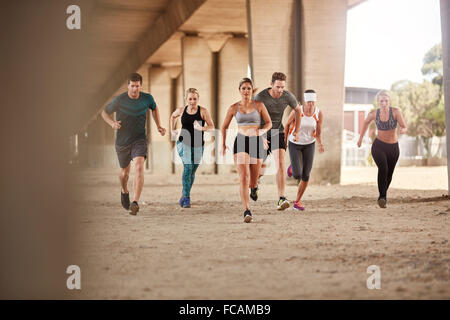 Portrait of group of runners in fitness clothing running under a bridge. Young men and women doing running work - Stock Photo