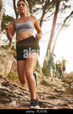 Healthy young athlete running outdoors. Female trail runner training for marathon run with people in background. - Stock Photo