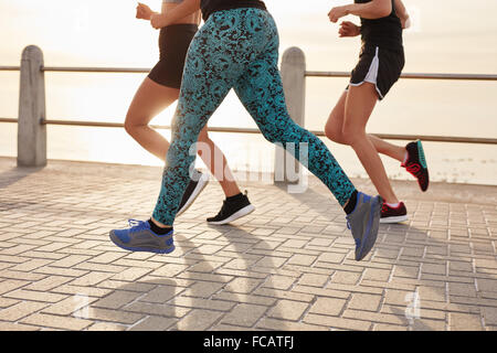 Cropped image of young people running along the sea. Fitness group doing running workout together outdoors. - Stock Photo