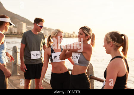 Runners relaxing after finishing the race. Marathon race runners taking a break after a run. - Stock Photo