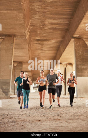 Portrait of healthy young people running under a bridge. Running club group wearing sport clothing training in the - Stock Photo