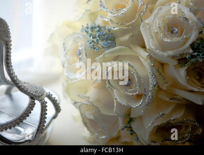 Bride's shoes and bouquet on a white background. - Stock Photo