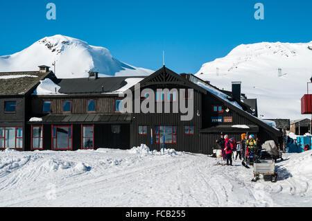 Train station Finse, railway Oslo-Bergen, tourists on ski, mountain Finsenuten in the back, winter, Hordaland, Norway - Stock Photo