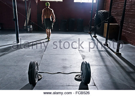A crossfit athlete racks his weights after working out. - Stock Photo