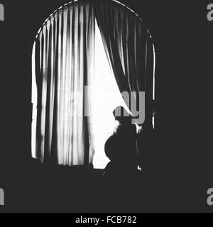 Side View Of A Pregnant Woman Standing At Window - Stock Photo