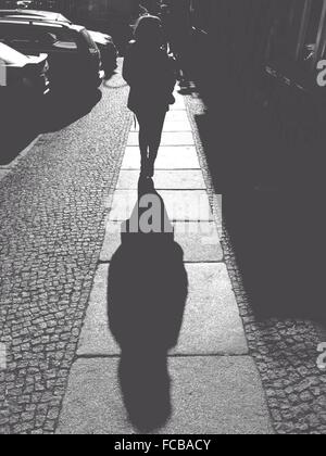 Rear View Of Woman Walking On Sidewalk During Sunny Day - Stock Photo
