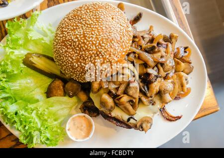 A dish with a hamburger with sauteed mushrooms on top, sesame bun bread, letuce and mayonaise. A delicious grilled - Stock Photo