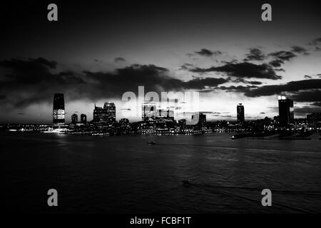 A panoramic view of Jersey City shore at night in Jersey City, New Jersey, USA. - Stock Photo