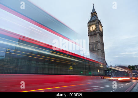 Big Ben in the early morning and red bus passing in London, natural colors - Stock Photo