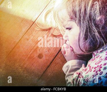 Close-Up Of Cute Young Girl Sleeping On Wooden Surface
