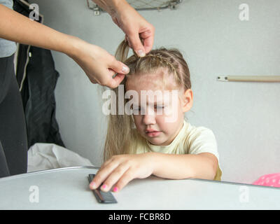 Young mother combing her long hair a four-year daughter on a cot in a train - Stock Photo