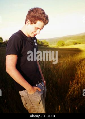 Side View Of A Smiling Young Man On Landscape - Stock Photo