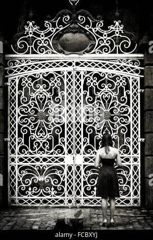Rear View Of Woman Standing In Front Of Large Closed Gates - Stock Photo