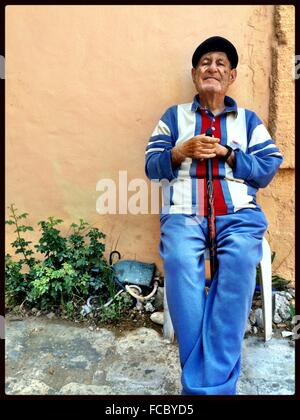 Old Man Sitting In Front Of Wall - Stock Photo