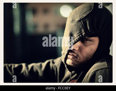 Close-Up Of Man Wearing Winter Hood And Looking Sad - Stock Photo