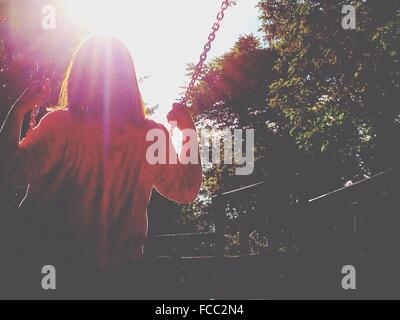 Rear View Of Girl Swinging On Sunny Day - Stock Photo