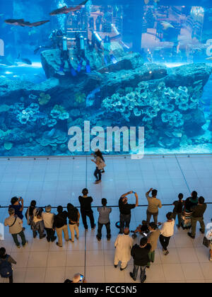 Dubai mall - shoppers in front of aquarium attraction. - Stock Photo