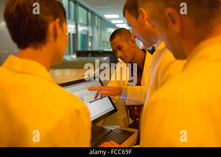Engineers around computer in factory - Stock Photo