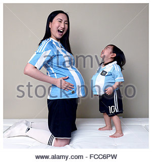 Happy Daughter Imitating Pregnant Mother At Home - Stock Photo