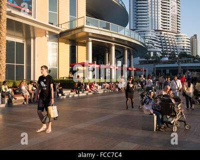 Tourists, immigrant workers, local residents on waterfront promenade in Dubai Mall, UAE. - Stock Photo