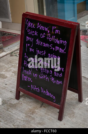 An aspirational quotation of Mitch Hedberg, comedian, hand written in purple chalk pen on an A-board sign - Stock Photo