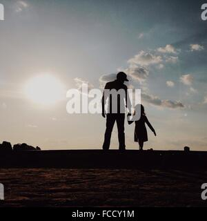 Silhouette Father With Daughter Standing On Field Against Sky Stock Photo